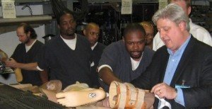Peter Rosenberger training inmates on disassembling prosthetic limbs in order to recycle the components.